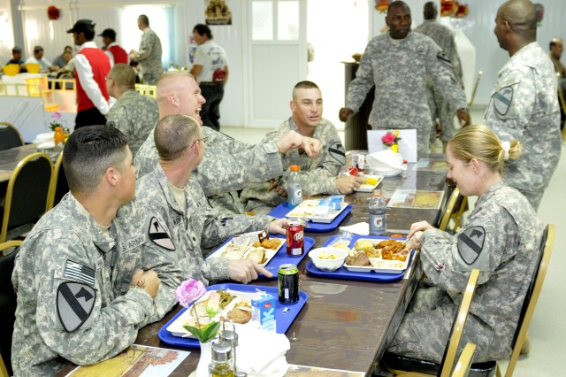 CONTINGENCY OPERATING SITE IRBIL, Iraq-Soldiers assigned to the 5th Battalion, 82nd Field Artillery, 4th Advise and Assist Brigade, 1st Cavalry Division, enjoy Thanksgiving dinner together while deployed.  The Black Dragon battalion recently deployed in support of Operation New Dawn, and the Soldiers are celebrating their first major holiday away from their Families by celebrating together.