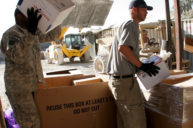 An oversized fork lift brings in pallets of mail in the background as postal workers with the 328th Human Resources Company sort holiday packages at the Army Post Office on Kandahar Airfield, Nov. 25.