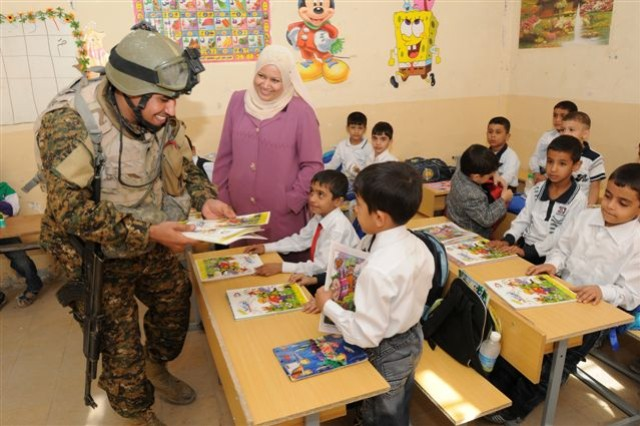 An Iraqi Army Soldier passes out books to the children of Al Fatih Al Mubien Primary School in Al Zharnar District, Basra. The civil military operation, advised and assisted by United States Division-South Soldiers, supports the IA in establishing community relationships with its people.