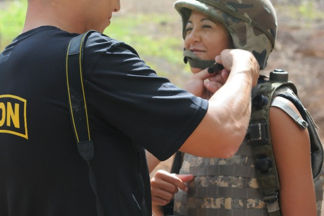 Christopher Bluhm, company commander for Headquarters andHeadquarters Co., 3rd BN, 25th INF Regt., helps his wife, Ida, don a Kevlar