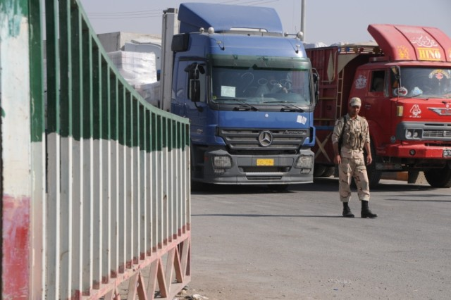 BASRA, Iraq - An Iranian border guard supervises the orderly passage of trucks, full of manufactured goods and produce bound for Iraq, at the Shalamsha Port of Entry.