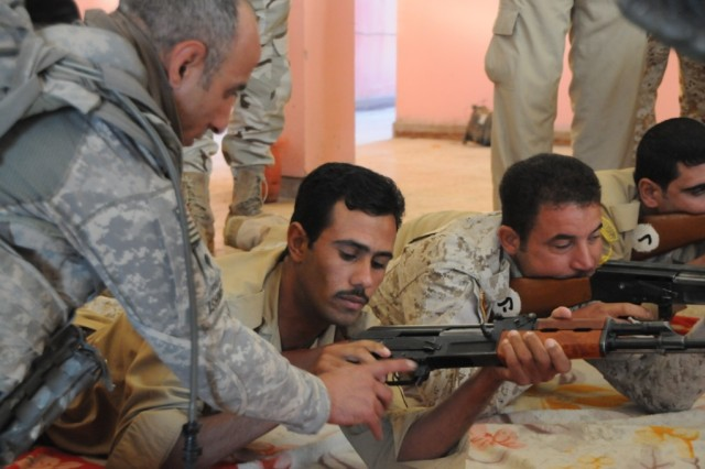 BASRA PROVINCE, Iraq-A Soldier from Troop B, 4th Sqdn., 10th Cav. Reg. 3rd AAB, 4th Inf. Div. assists a member of the Iraqi Department of Border Enforcement with basic rifle marksmanship at a DBE outpost along the border between Iraq and Iran.  Troop B Soldiers conduct frequent training with the DBE to enable them in their mission to provide security and sovereignty of the border.