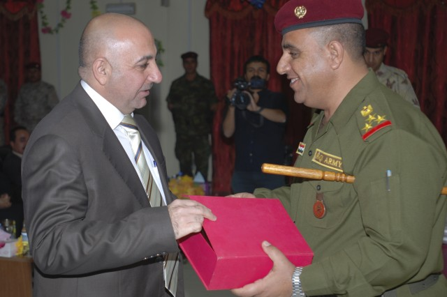 101118-A-1121F-002.jpg - BAGHDAD - Director for Regional Guard Brigade Intelligence and Commandant of the Iraqi Army Intelligence School, Staff Brig. Gen. Abdul Khalek, presents gifts to distinguished visitors during a graduation ceremony for the school's specialty courses in Camp Taji, Nov. 15.