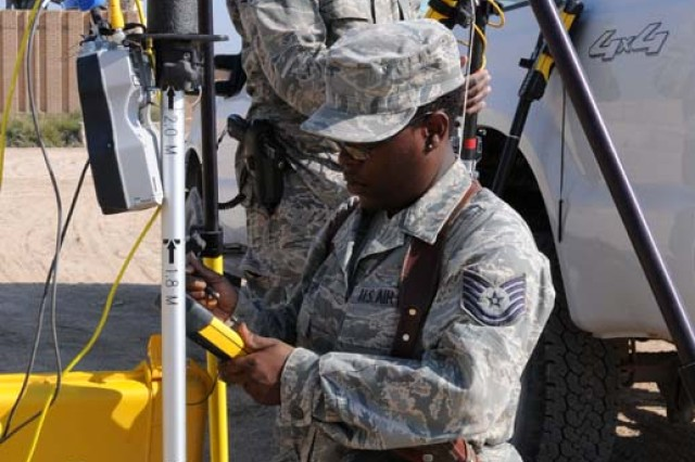 U.S. Air Force Tech. Sgt. Andrea Romero, Lead Assistant Engineer and Sen. Airman Cory Montgomery, Assistant Engineer, both of the Contingency Operating Site Kalsu Facility Engineer Team, 467th Expeditionary Prime Base Engineering Emergency Force, prepare survey equipment on COS Kalsu Nov. 24. The two are surveying land that will be used as living and working space for Iraqi Army Soldiers. The FET performs an array of survey and master planning duties alongside Army engineers on Kalsu.