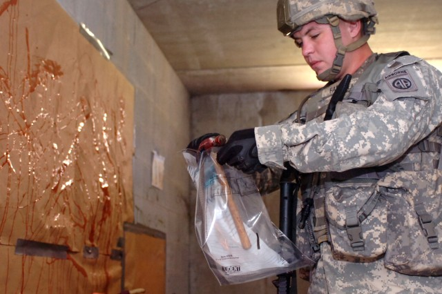 Standing in the middle of a simulated torture chamber, Spc. Jonathan Farrell, a military police Soldier, with Headquarters, 2nd Brigade Special Troops Battalion, places a bloody clawed hammer in an evidence bag.