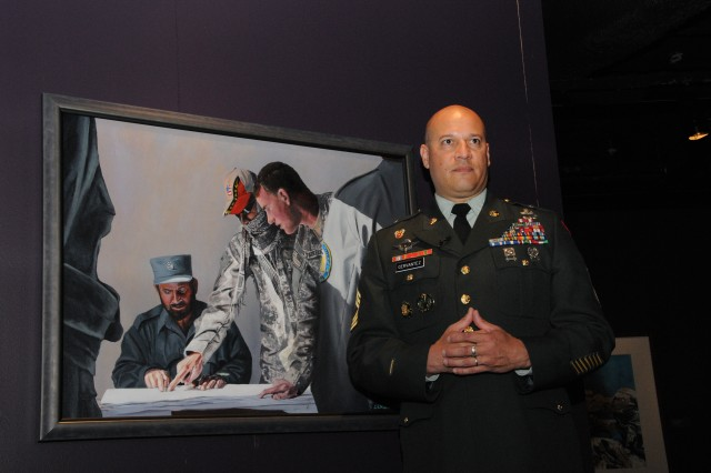 """Master Sgt. Martin Cervantez stands in front of his painting, """"A Huge Responsibility."""" Cervantez is the artist-in-residence at the Center of Military History at Fort McNair in Washington, D.C."""
