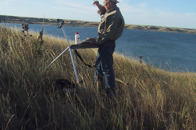Jim Pollock, a former combat artist, paints a landscape in plein-air in this recent photo.
