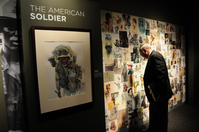 A museum patron examines a wall of sketches from various combat artists in the Art of the American Soldier exhibit, on display through Jan. 10, at the National Constitution Center in Philadelphia.