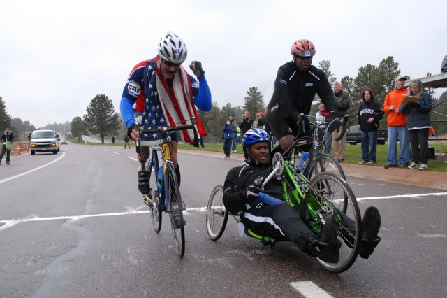 Left to right: Navy Master Chief Petty Officer Will Wilson, Sgt. Monica Southall and Warrant Officer Johnathan Holsey near the finish line after a grueling Warrior Games cycling competition at the U.S. Air Force Academy in May. After noticing Southall struggling to finish, Wilson and Holsey abandoned their race and remained to help her finish.