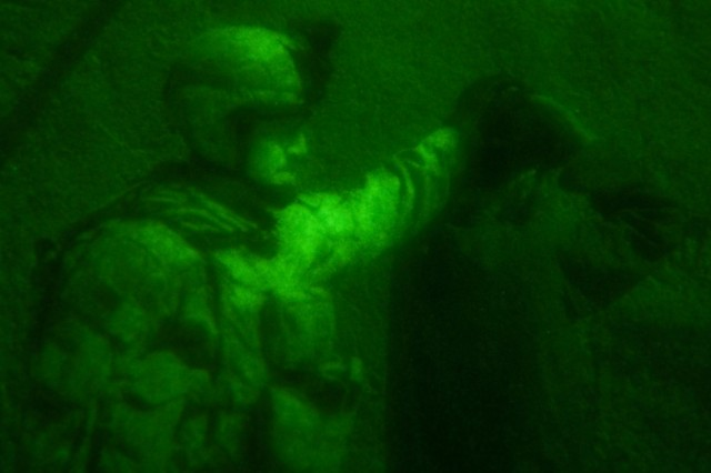 Cpl. Christopher Noc, a team leader for Company H (Hawk Co.), 3rd Squadron, 2nd Striker Cavalry Regiment, secures a detainee during a night raid Nov. 22, in the Maiwand District of Afghanistan. Evidence was found to suggest that insurgents from a recent engagement fled to the raided compounds for medical attention.