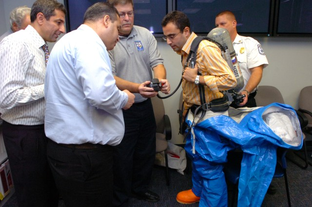 Members of the Cecil County, Md., Department of Emergency Services discuss details of hazardous materials protective equipment with Capt. Jalal Kasaouati (in suit) and Lt. Col. Mohamed El Haouri (left) of the Moroccan Army during a tour of CBRNE response facilities, Nov. 17, 2010.