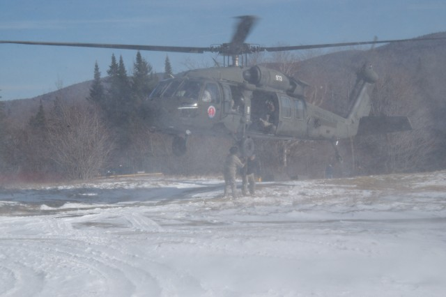SPECULATOR, NY-- New York Army National Guard Aviators brave the cold windblown snow thrown up by the UH-60 rotorwash as they prepare to slingload 2000 pound helipad components during a mission to assist the New York State Department of Environmental Conservation on Monday, Nov. 29. The helipad will allow state aircraft to service a radio repeater being erected on Wakley Mountion in the heart of the Adirondacks.