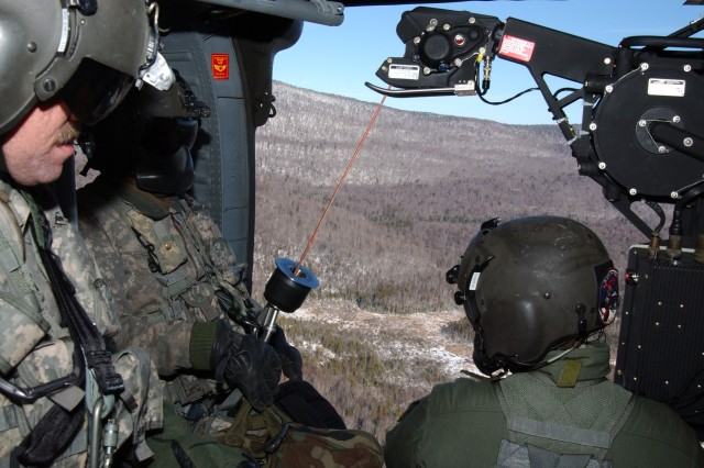 SPECULATOR, N.Y. -- New York Army National Guard Aviation Soldiers from Army Aviation Support Facility 3 based in Latham, NY prepare to be hoisted down into a forest clearing to assist New York Department of Environmental Conservation (DEC) workers on Nov. 29 to place airlifted helipad platform sections at the top of Wakely Mountain.The airlifted platforms will allow the DEC to eventually construct a helipad as well as a repeater radio station on top of the mountain that will be used by the DEC and other state agencies.Each platform weighed more than 2000 pounds and were constructed in Colorado and flatbed delivered to the Adirondacks