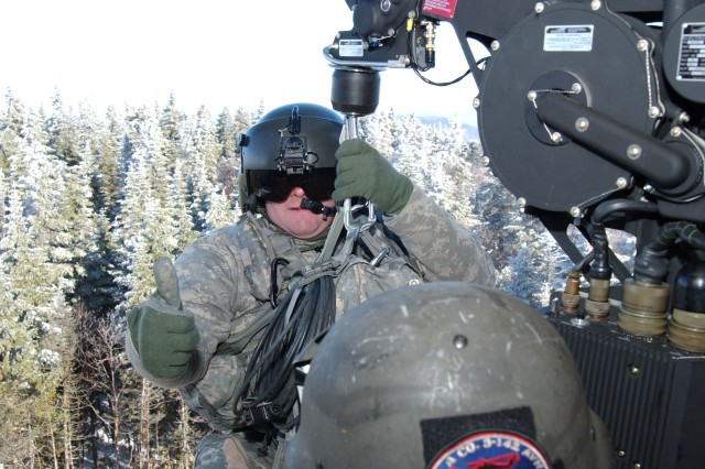 SPECULATOR, NY--A New York Army National Guard Aviator Staff Sgt Donald Smithgall gives the thumbs up as he makes ready to be lowered to the top of 3,750-foot high Wakley Mountain in the heart of the Adirondack Mountains on Monday, Nov. 29. The Soldiers were assisting the New York State Department of Environmental Conservation by transporting helipad components to the top of the mountain.