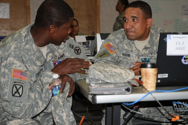 3rd Sustainment Command (Expeditionary) ammunition inspector and Mount Dora, Fl. native, Staff Sgt. David Gilmore, talks with 7th Sustainment Brigade munitions materiel management officer and New York City native Capt. Ariel Rivera during the brigade's mission readiness exercise at Fort Bragg, N.C. on Nov. 11.  About 40 3d ESC Soldiers spent two weeks at Fort Bragg's Battle Command Training Center making sure the 7th Sus. Bde. was ready for its upcoming deployment to Afghanistan.  (U.S. Army photo by Spc. Krista Payne)