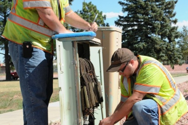 John Mayfield (left) and Troy Richmeier inspect a cable pedestal to isolate and tone specific cables for locating and marking for a dig permit. The Fort Carson NEC recently received honors as the 7th Signal Command (Theater) NEC of the Year (Large Post).