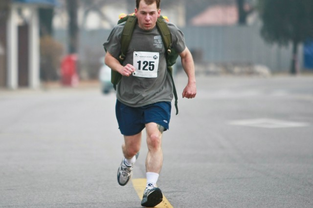 Jeffrey Hayden, a 33-year old sergeant from HHC, 2nd Battalion, 9th Infantry Regiment, charges toward the finishline and first place in the rucksack challenge.