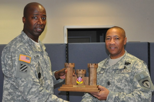 Command Sgt. Maj. David M. Clark, the command sergeant major for the 18th Engineer Brigade and a native of Knoxville, Tenn., presents Command Sergeant Major Thomas R. Capel, the command sergeant major for U.S. Army Europe and a native of Ellerbe, N.C., with an 18th Eng. Bde. castle Nov. 23 at Tompkins Barracks. Capel visited the 18th Eng. Bde. and spoke with Soldiers about their quality of life and preparation for their upcoming deployment.