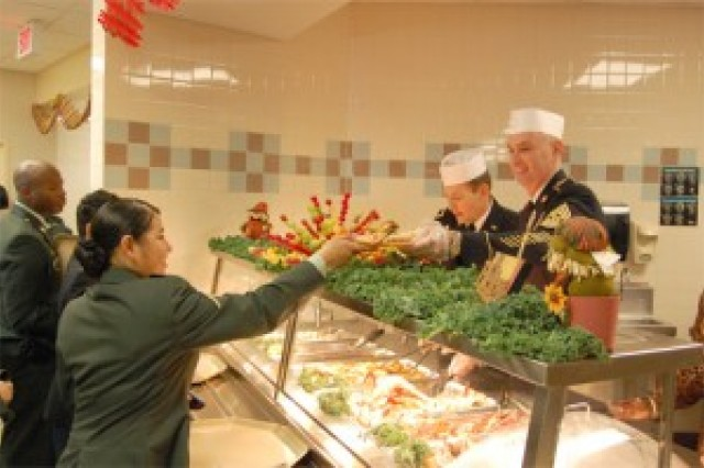 An advanced individual training student places an order for crab legs and ham with Brig. Gen. Edward F. Dorman III, Transportation Corps commanding general, and Command Sgt. Maj. Dwayne Perry, Transportation Corps regimental command sergeant major, during the Thanksgiving Day meal at a dining facility on post.   ""