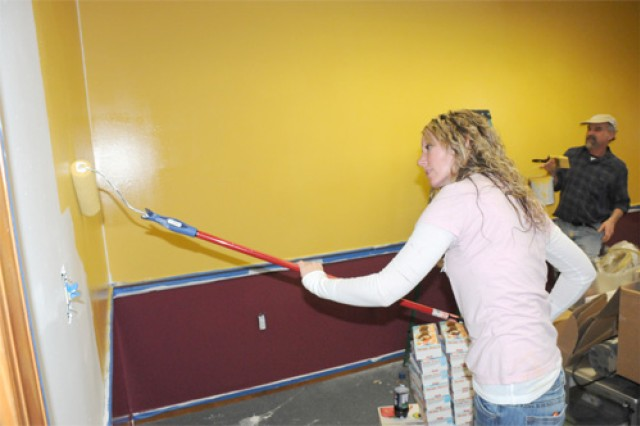 Kharon Morris, Marine spouse and Prince George Lowe's employee, paints the walls of the new Fort Lee USO Monday. Lowe's and USO are working together to remodel several centers across the country.