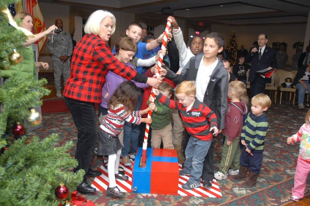 Military children help Dee Thurman, wife of Gen. James Thurman, commanding general, U.S.Army Forces Command, pull a candy cane lever to light three Christmas trees during Fort McPherson's tree-lighting ceremony held at The Commons at Fort McPherson Tuesday. The ceremony, which was hosted by Col. Deborah Grays, U.S. Army Garrison commander, and attended by Atlanta Mayor Kasim Reed, served as the official start to the fort's holiday season.