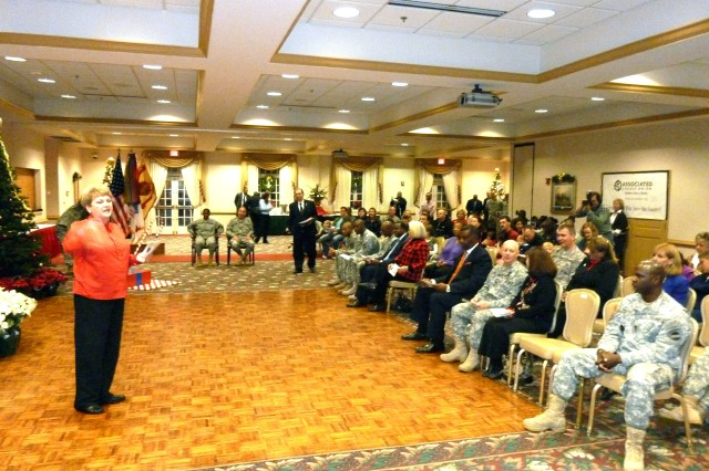 """Donna Craven, director of religious education, U.S. Army Garrison Chaplain Office, leads members of the audience in a rendition of Aca,!A""""Rudolph the Red-Nosed Reindeer.Aca,!A?"""