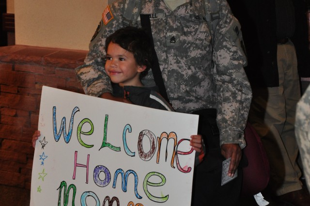 Staff Sgt. Tomina Hall poses with her son Ajohnny as he holds up the poster he brought to the airport to welcome her home.