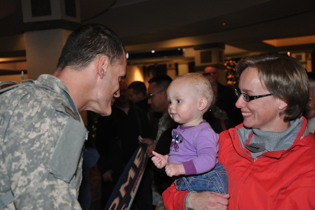Capt. David Keithan greets his young daughter Nina and his wife Jeannette at the Colorado Springs Airport after a yearlong deployment with Army Space Support Team 6.