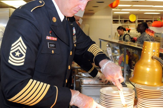 Sgt. Maj. Keith Cooper, 1st Bn., 223rd Avn. Regt., carves a beef roast during the annual Thanksgiving meal for Soldiers at the dining facilities Nov. 24.