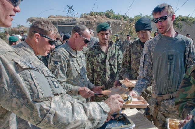 Soldiers from Company A, 1st Battalion, 187th Infantry Regiment, 3rd Brigade Combat Team, 101st Airborne Division (Air Assault) wait in line for Thanksgiving dinner in Panjwa'i, Afghanistan. The meal was a welcome luxury for the Soldiers whose usual diet consists of Meals-Ready-To-Eat, prepackaged combat meals. (U.S. Army photo by: SPC Edward Garibay, 16th Mobile Public Affairs Detachment.)