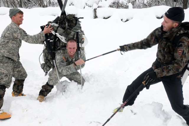 BOHINJSKA BELA, Slovenia --  A heavily laden Soldier with U.S. Army Europe's 172nd Infantry Brigade gets back on his feet with help from a buddy and a Slovenian instructor during training at the Slovenian Armed Forces Mountain Training Center here, Dec. 2. Soldiers from the 172nd are participating in a weeklong mountain warfare training program at the school. For more photos of the training and other USAREUR images, visit www.flickr.com/photos/usarmyeurope_images.