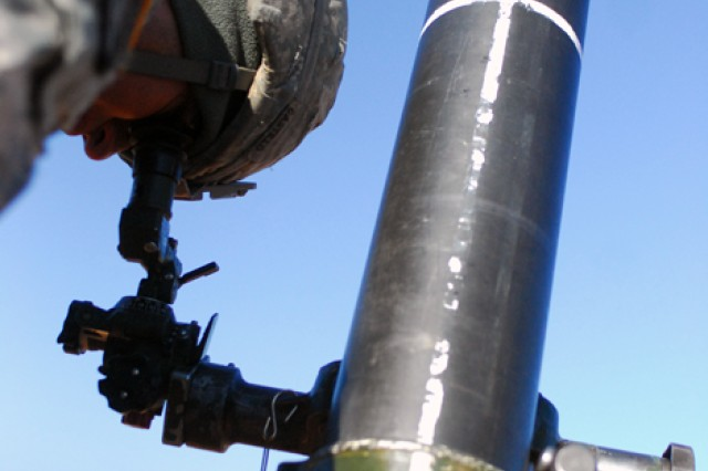 A mortarman uses sights on a mortar tube as a team prepares to hit a simulated target during training Wednesday at Cactus Range.