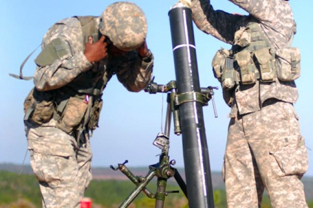 A two-man team loads mortar rounds before firing downrange.