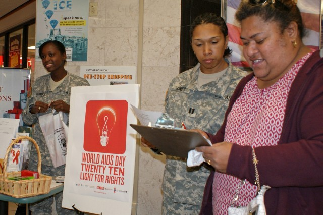 """FORT HOOD, Texas - Testing her knowledge on HIV and AIDS, Fia Leiato (right) fills out a quiz created by Carl R. Darnall Army Medical Center's Public Health Nursing department, as part of its observance of World AIDS Day Dec. 1.  More than one million people live with HIV and an estimated 56,300 people in the U.S. will be infected this year, according to data from the Joint United Nations Program on HIV/AIDS. Countries around the globe participated in various World AIDS Day activities to reinforce the HIV prevention message.  CRDAMC public health nurses Capt. Lakeisha Jones (center) and Capt. Tranessia Murphy set up at the Clear Creek PX during lunch and used the quiz, along with informational brochures and condoms, to help educate the Fort Hood community on HIV/AIDS.  """"It's just so important that everyone knows about the risks and health issues associated with AIDS. We give briefings four days a week to Soldiers and thought we would be able to reach a wider audience by setting up over here,"""" Murphy said.   Jones added that the only way to know for sure if you have HIV is to get tested.   """"It's especially important to get tested at least once a year if you are at high risk of infection.  You could have HIV and still feel healthy,"""" she said.  """"Many doctors recommend HIV testing for all teens and adults between the ages of 13 and 64. You can call any one of our five Communicable Disease Services clinics to schedule an appointment for a test. All test results are confidential."""""""