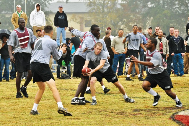 Geoffrey Uhal, center, of the officers looks for a teammate as senior NCO defenders converge Nov. 24 during the 11th Engineer Battalion's annual Turkey Bowl at Stewart-Watson Field. The officers scored twice in overtime to pick up a 10-8 victory, their fourth straight win in the ultimate football showdown.
