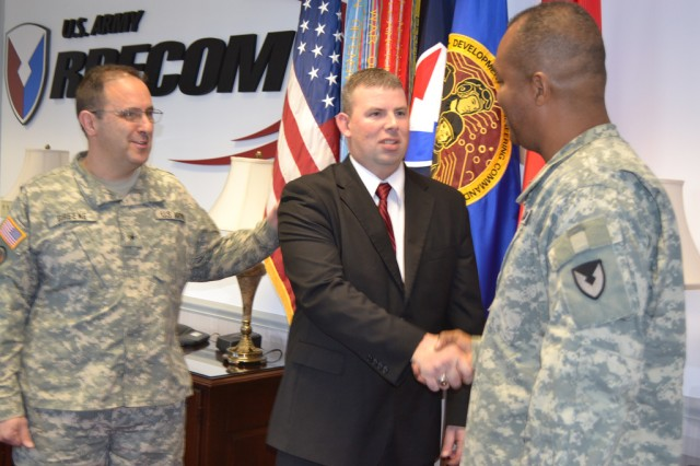 Retired Staff Sgt. Mitch Court receives U.S. Army Research, Development and Engineering Command coins from Deputy Commanding General Brig. Gen. Harry Greene, left, and Command Sgt. Maj. Hector Marin, who also presented Court with a camouflaged backpack.  A veteran of three combat tours to Iraq, Court visited the RDECOM and Engineering Command headquarters Dec. 3.