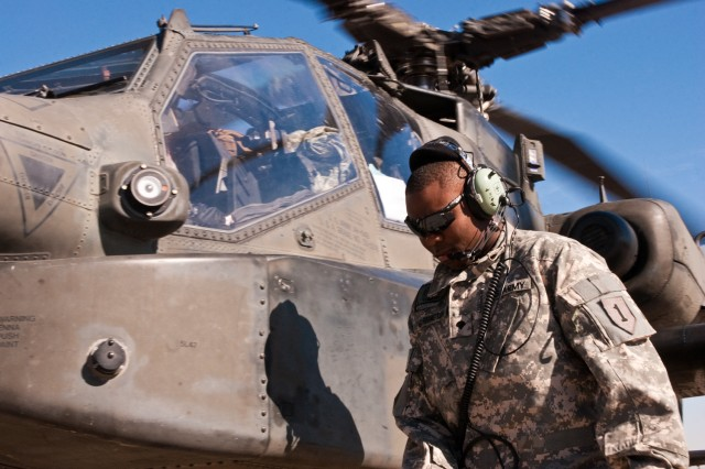 Spc. Kiwanuas Harrington, an Apache helicopter crew chief serving in Iraq, circles his aircraft after it returns from a mission in the Baghdad area, Dec. 1. Harrington and his peers are responsible for repairing and maintaining Apaches from the 1st Attack Reconnaissance Battalion, 1st Aviation Regiment, the only Apache unit deployed to Iraq. (U.S. Army photo by Spc. Roland Hale, eCAB, 1st Inf. Div. PAO)