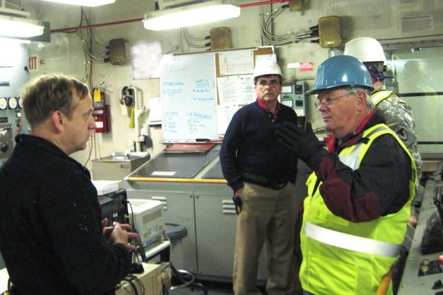 Gordon Bonham, (right) 406th Army Strategic Logistics Activity, Charleston, S.C., talks with Chief Engineer Bill Maus and Captain Chris Larkin aboard the USNS Watson as it is docked at Gwangyang port in the Republic of Korea on Dec. 4.