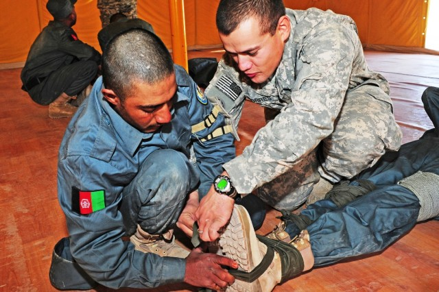 An Afghan National Police recruit looks on as Spc. Edwin Torres, a combat medic with Headquarters & Headquarters Company, 1st Squadron, 2nd Stryker Cavalry Regiment, demonstrates the proper way to tie a knot during the splinting process Nov. 30. All ANP recruits receive combat medical training prior to graduating from the Afghan National Police Training Center at Multi National Base Tarin Kot, Afghanistan. (U.S. Army photo by Spc. Jennifer Spradlin, 16th Mobile Public Affairs Detachment)