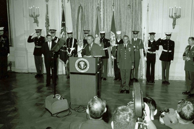 President Lyndon B. Johnson presented the first  Medal of Honor of the Vietnam War to Captain Roger H. C. Donlon (standing right, at attention) at the White House on December 5, 1964, for actions above and beyond the call of duty while at Camp Nam Dong in Vietnam.