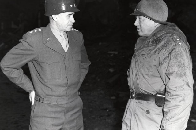 Lt. Gen. Omar N. Bradley and Lt. Gen. George S. Patton confer and stand among the ruins of the shattered city of Bastogne, Belgium, February 5, 1945.