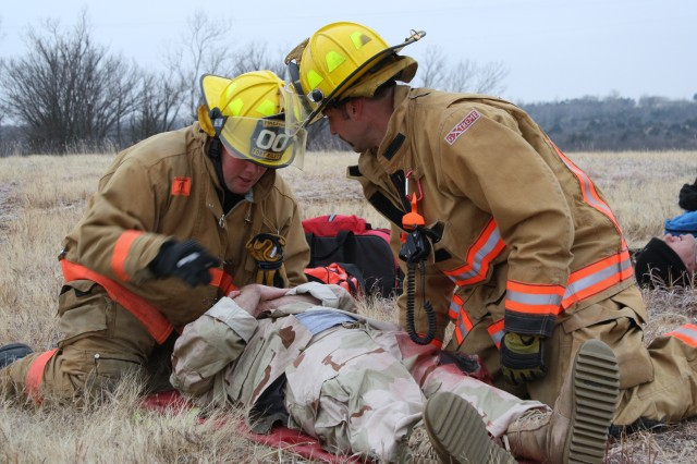 Fort Riley Fire Department firefighters Daniel Lawton, left, and Justin Schmidt, right, move an injured person to a back board for transport to Irwin Army Community Hospital  Nov. 23 during a mass casualty exercise at the Ammunition Supply Point.
