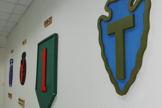 A wooden replica of the 36th Infantry Division patch adorns the wall of a United States Division-South headquarters hallway. The patch is next to the patches of units who previously served as the Multinational Division-South and USD-S headquarters, including the 1st Infantry Division's.