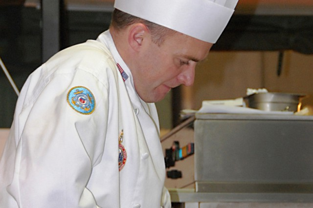 Senior Chief Justin Reed cuts the meat for the main course during the Culinary World Cup's hot kitchen competition in Luxembourg. The team placed third overall in the competition.