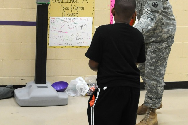 Sergeant 1st Class Aaron Loos, a maintenance management noncommissioned officer with the 3d Sustainment Command (Expeditionary), hands a basketball to a student during the Pierce Elementary School Winter Festival Dec. 2. Sergeant 1st Class Loos was one of 25 Sustainers who volunteered at the school's festival. (U.S. Army photo by Staff Sgt. Rob Strain)