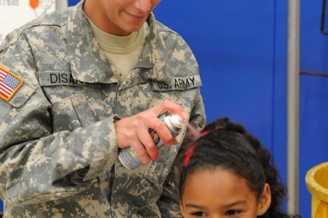 Sergeant Christina Disano, a driver with the 3d Sustainment Command (Expeditionary), sprays the hair of Taliyah Villanueva, 6, during the Pierce Elementary School Winter Festival Dec. 2. Disano was one of 25 Sustainer Soldiers who volunteered their time to support the school during the event. (U.S. Army photo by Staff Sgt. Rob Strain)