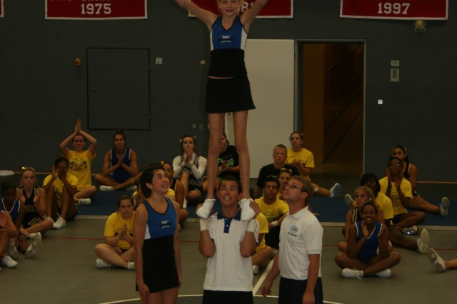 Josh Rivera hoists Kirsten Atkinson over his head while fellow All-American Meagen Dunleavy cheers them on.