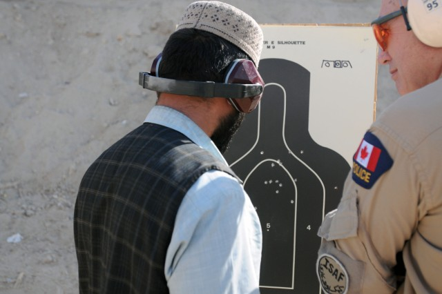 CAMP NATHAN SMITH, Afghanistan-- Constable Lorant Haged, Royal Canadian Mounted Police officer and instructor at the Officer and Leaders Management Course, looks at a target after the ANP ceased fire at a 9mm familiarization range Dec. 3. The ANP are attending the six-month training course where they will also take a criminal investigation course, leadership and management classes and rule of law. The intent of the school is teach ANP officers and leaders at an advanced level of training that will help them become more effective in running police sub-stations. (Photo by: Staff Sgt. LaSonya Morales, 16th Mobile Public Affairs Detachment)