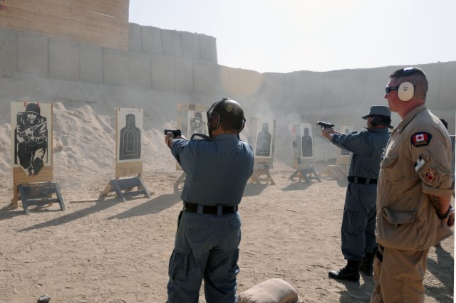 CAMP NATHAN SMITH, Afghanistan-- Constable Lorant Haged, Royal Canadian Mounted Police and instructor at the Officer and Leaders Management Course, observes Afghan National Police as they shoot at targets on a 9mm familiarization range Dec. 3. The ANP are attending a six-month OLMC focusing on teaching them how to be efficient in managing police sub-stations. (Photo by: Staff Sgt. LaSonya Morales, 16th Mobile Public Affairs Detachment)