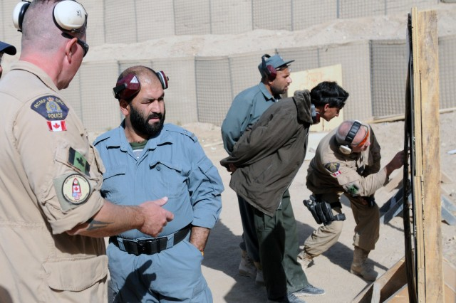 CAMP NATHAN SMITH, Afghanistan-- Constable Lorant Haged, Royal Canadian Mounted Police and instructor at the Officer and Leadership Management Course, coaches an ANP at a 9mm familiarization range Dec. 3. The ANP are attending the six-month OLMC where they will also take a criminal investigation course, leadership and management classes and rule of law. The intent of the school is teach the ANP officers and leaders at an advanced level of training that will help them become more effective at running police sub-stations. (Photo by: SSG LaSonya Morales, 16th Mobile Public Affairs Detachment)